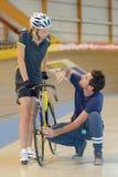 Female athlete training in velodrome with coach. Female athlete training in the velodrome with coach Royalty Free Stock Photos