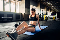 Female athlete trains press in sport gym. Young woman in fitness club Stock Photography
