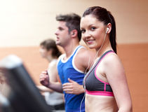 Female athlete on a treadmill with headset. In a fitness center Royalty Free Stock Photos