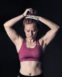 Female Athlete Tying Hair. Sportswoman Dark Gritty Strength & Determination Stock Photography