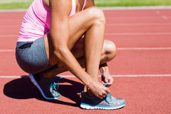 Female athlete tying her running shoes Royalty Free Stock Photos