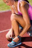 Female athlete tying her running shoes Royalty Free Stock Photo