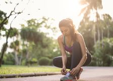Female athlete tying laces for jogging on road Runner getting ready for training. Sport lifestyle. Barefoot running shoes closeup. Female athlete tying laces for stock images