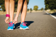 Female athlete tying sportshoes laces for running. On road. Runner getting ready for training Royalty Free Stock Photography