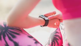 Female athlete using fitness app on her smart watch to monitor workout performance. Close-up Shot. Female athlete using fitness app on her smart watch to monitor Stock Photo