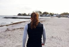 Female athlete walking on beach Stock Photo