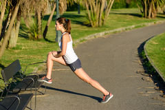 Female athlete warming up and stretching for running. Female brunette athlete warming up and stretching legs before running outdoor in park. Fitness woman Stock Photography