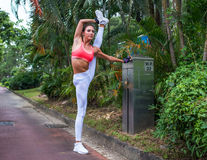 Female athlete warming-up before working-out stretching her legs doing standing split exercise outdoors in park in Royalty Free Stock Photos