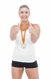 Female athlete wearing a medal and showing thumbs up Royalty Free Stock Images