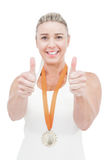 Female athlete wearing a medal and showing thumbs up Royalty Free Stock Photography