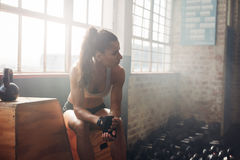 Female athlete woman having a rest after exercise at gym Stock Photos