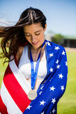 Female athlete wrapped in american flag with gold medal around her neck. In stadium Stock Images
