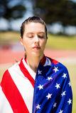 Female athlete wrapped in american flag. After victory Stock Images