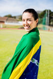 Female athlete wrapped in Brazilian flag. Portrait of female athlete wrapped in Brazilian flag Royalty Free Stock Photography