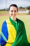 Female athlete wrapped in Brazilian flag. Portrait of female athlete wrapped in Brazilian flag Royalty Free Stock Photo