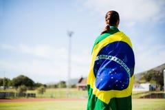 Female athlete wrapped in Brazilian flag. Rear view of athlete wrapped in Brazilian flag Royalty Free Stock Photos