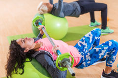 Female athletes doing barbell chest press lying on a Swiss ball during group training in fitness center Stock Photos