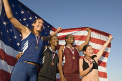 Female Athletes Holding American Flag Against Blue Sky Royalty Free Stock Photo