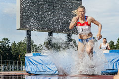 Female athletes leader of  race at steeplechase Stock Image