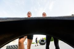 Female Athletes Lifting Tire Outdoors Stock Photos