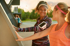 Female athletes stretching before going jogging outdoors royalty free stock photos