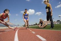 Female Athletes Stretching Before Race Stock Image
