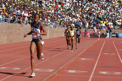 Female athletic race. Black women competing in athletic running race on stadium track with crowd in background stock photography