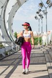Fit middle-aged woman walking after training in park. Female athletic runner in park in the summer, walking after a jog, fitness and healthy lifestyle concept Stock Image