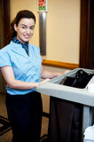 Female attendant posing with cart Royalty Free Stock Photography