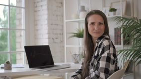 Female attorney business owner lawyer posing for photo in cozy office. Young creative specialist sitting at the table with brand-new computer, looking to the stock video