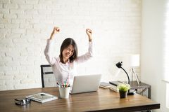 Female attorney celebrating good news. Excited woman using the computer and celebrating some good news with her arms up Royalty Free Stock Photo
