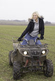 Female on ATV. Happy female on an ATV in the field Stock Image