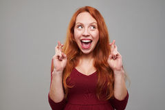 Female with auburn hair keeping her fingers crossed Stock Photo