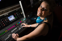 Female audio engineer using sound mixer in recording studio Stock Photos