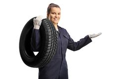 Free Female Auto Mechanic Carrying A Tire On Her Shoulder Stock Photography - 216189412
