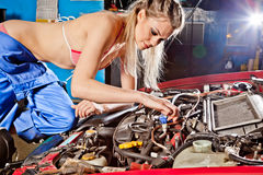 Female auto mechanic repairing a car Royalty Free Stock Images