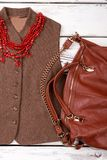 Female autumn outfit with purse and necklace. Cropped vertical view jacket with necklace and satchel Royalty Free Stock Photos