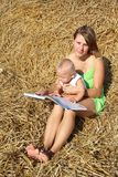 Female with a baby reading a book on a haystack Royalty Free Stock Image