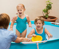 Female baby-sitter with little girls at pool Royalty Free Stock Photos
