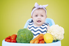 Female baby with vegetables on high chair Royalty Free Stock Photo