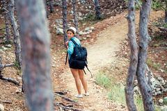 Female with backpack trekking on mountains, walking and running through forest and hills. Happy woman, ready for adventure Stock Image