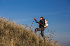 Female backpacker ascends steep hill Stock Photography
