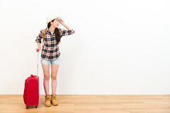 Female backpacker carrying travel luggage suitcase. Smiling pretty female backpacker carrying travel luggage suitcase standing on wooden floor with white Stock Photography