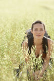 Female Backpacker Crouching In Field Of Grass Stock Images