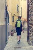 Female backpacker exploring narrow streets of medieval town. stock photography