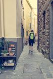 Female backpacker exploring narrow streets of medieval town. royalty free stock photography