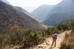 Female backpacker hikes trail. On route to Everest Base Camp Royalty Free Stock Photos