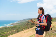 Female backpacker holding online travel guidebook. Smiling female backpacker holding online travel guidebook through digital tablet pad standing on hiking royalty free stock photography