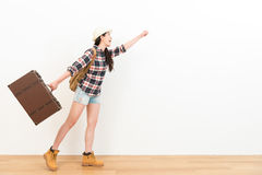 Female backpacker holding vintage suitcase. Beautiful cheerful female backpacker holding vintage suitcase standing on wooden floor and performed ready to start Stock Images