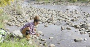 Female backpacker refreshing in creek stock video footage